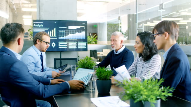 group of smart and respectable business people work on a problem solving in the meeting room. diverse group of mixed ethnicity and gender explore potential for company future development. - progettare video stock e b–roll