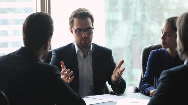 Group of smiling entrepreneurs establishing partnership, making agreement. Focused diverse business people holding negotiation meeting, shaking hands after coming to profitable decision deal. Group of smiling entrepreneurs establishing partnership, making agreement. business suit stock videos & royalty-free footage