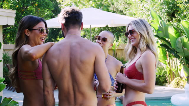 Group Of Smiling Friends Outdoors Drinking Beer And Enjoying Summer Pool Party