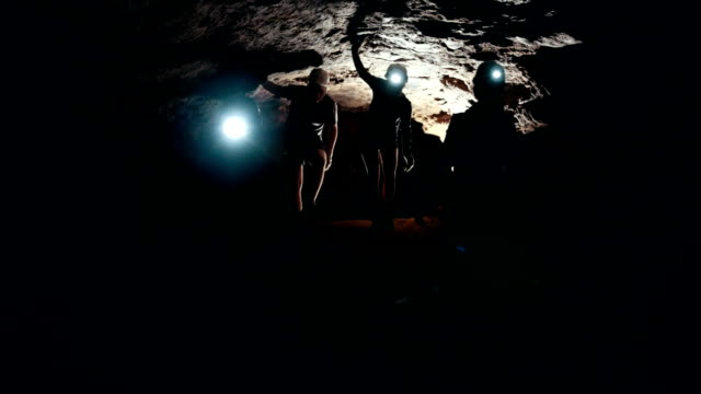group of speleologists explore the walls of the cave - speleologia video stock e b–roll