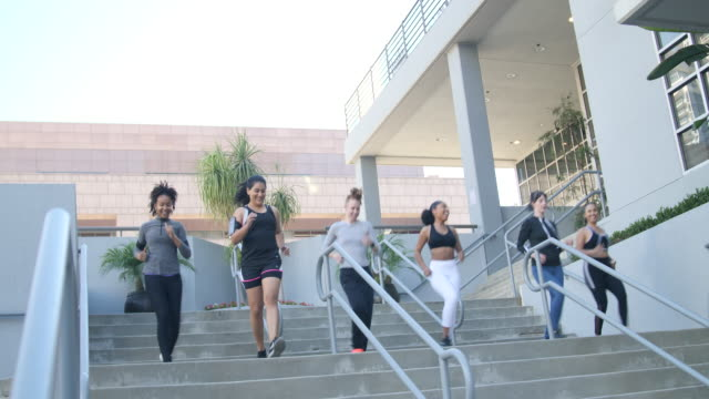 Group of sporty women running down the stairs
