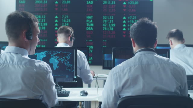 group of stockbrockers actively working at stock exchange - stock broker stock videos & royalty-free footage