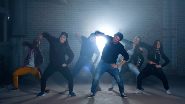 Group of street dancers performing different moves on the dark street Group of street dancers performing different moves on the dark street hip hop stock videos & royalty-free footage
