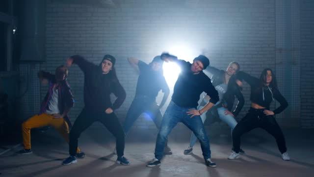 vidéos et rushes de groupe de danseurs de rue effectuant différents se déplace dans la rue sombre - hip hop