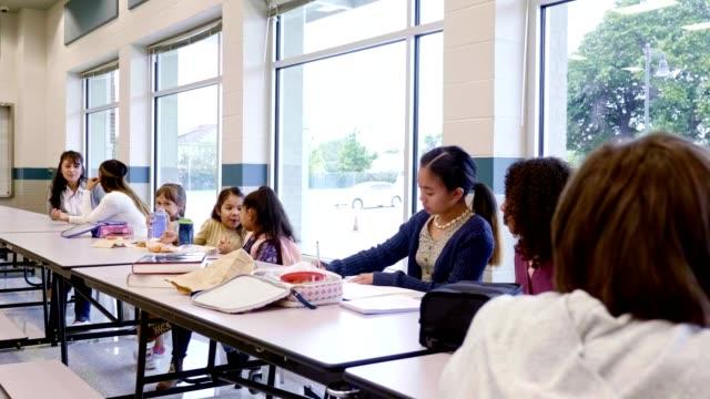group of students and teachers eating lunch in school cafeteria - stołówka filmów i materiałów b-roll