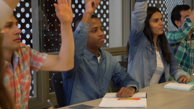 group of students at class in college raising hand and black student answering the question - rispondere video stock e b–roll