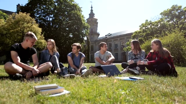 Group of students chatting on campus lawn video