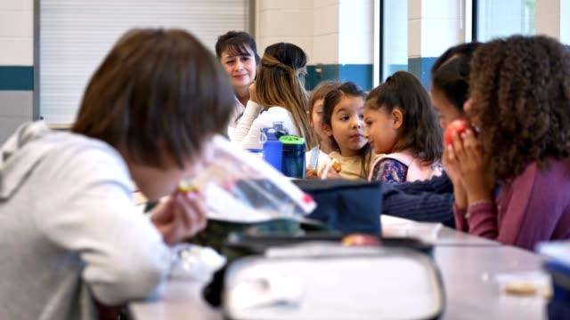vídeos de stock e filmes b-roll de group of students eat lunch in a school cafeteria - cantina