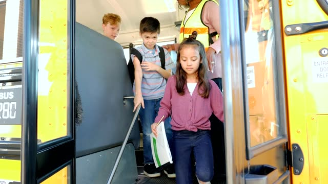 Group of students getting off of school bus Diverse group of mixed age school children unload a school bus. A mature female bus driver assists them as they get off of the school bus. school buses stock videos & royalty-free footage