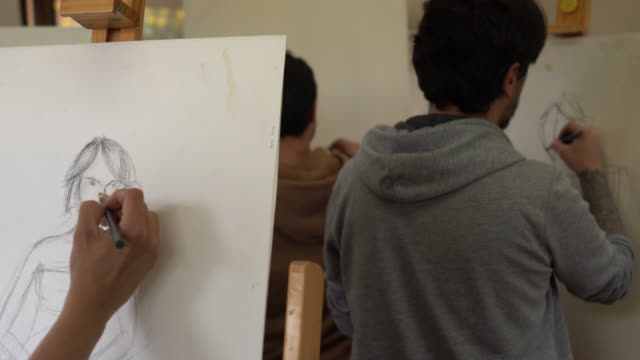 Group of students painting with charcoal while looking at a female model at the front of the class video