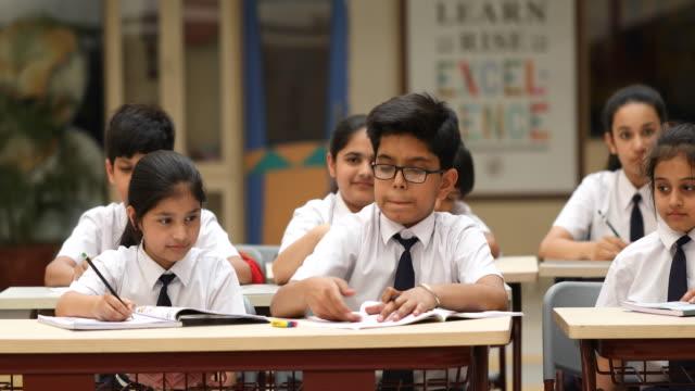 grupa uczniów studiujących książkę w klasie - uniform filmów i materiałów b-roll