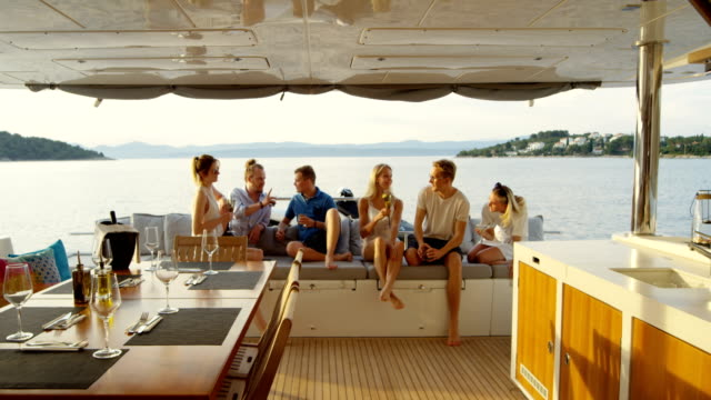 Group of Successful Young People Have Great Time in the Stern of a Yacht, They Drink Cocktails, Talk and Have Fun. In the Background Sea and Islands.
