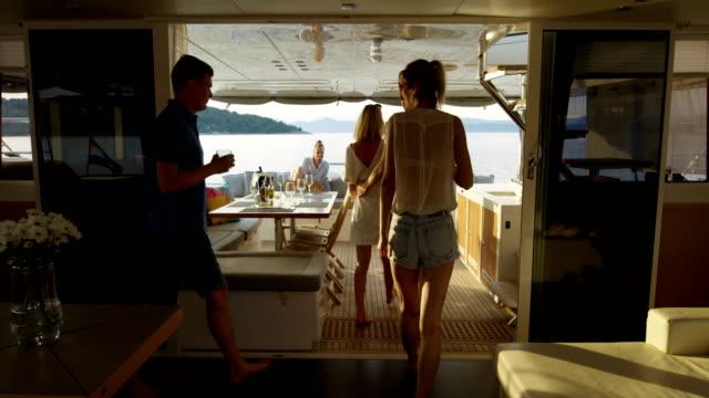 vídeos y material grabado en eventos de stock de grupo de jóvenes de éxito unirse a otros en la popa de la embarcación con cócteles. en las islas y calma mar de fondo. - yacht