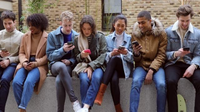 vídeos y material grabado en eventos de stock de grupo de amigos adolescentes se centró en su propio teléfono inteligente de mensajes de texto en las redes sociales - compartir