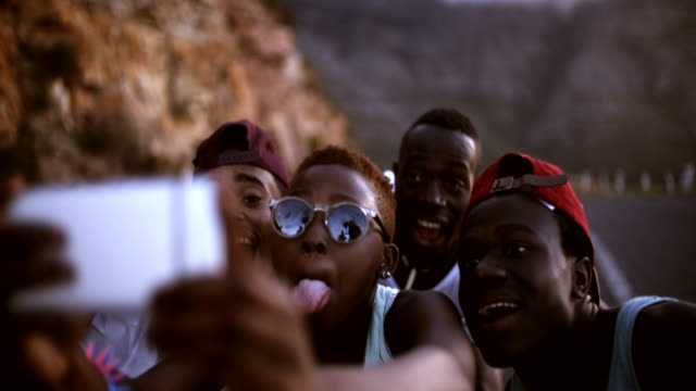 Group of teenage friends pulling faces for a selfie video