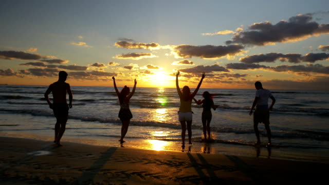 Group of teenage friends running and playing in water on the beach at sunrise video