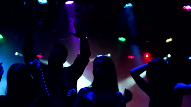 Group of teenagers dancing at concert. Silhouette. A group of teenagers dancing at the concert in the dark with smoke and lighting equipment. Silhouettes of dancing people having a celebration in a disco club. Slow motion. party stock videos & royalty-free footage