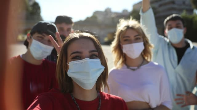 Group of teenagers posing showing their protective face masks - video