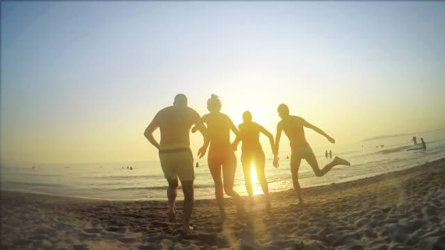 Gruppo di adolescenti di correre in acqua tramonto, Rallentatore, festeggia sulla spiaggia - video
