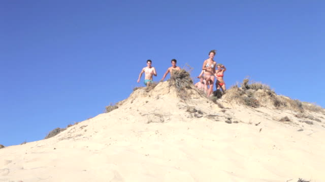 Group Of Teenagers Running Down Sand Dunes