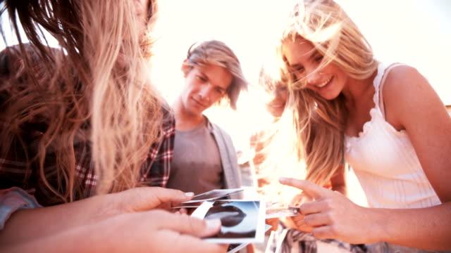 stockvideo's en b-roll-footage met group of teens sharing instant photographs - polaroid