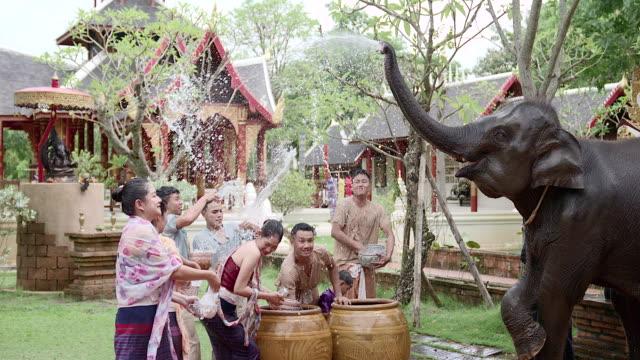 vídeos de stock, filmes e b-roll de grupo de meninos e de meninas tailandesas e de laos que espirram a água durante o festival festival songkran festival - ano novo budista