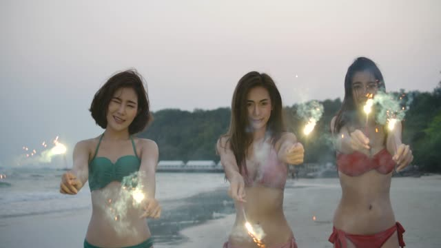 Group of three asian women in bikini having fun during night party at the seaside with bengal sparkler lights in their hands. Young teenagers partying on the beach with fireworks. Slow motion steadycam shot.