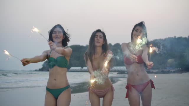 group of three asian women in bikini having fun during night party at the seaside with bengal sparkler lights in their hands. young teenagers partying on the beach with fireworks. slow motion steadycam shot. - фейерверк развлекательное мероприятие стоковые видео и кадры b-roll