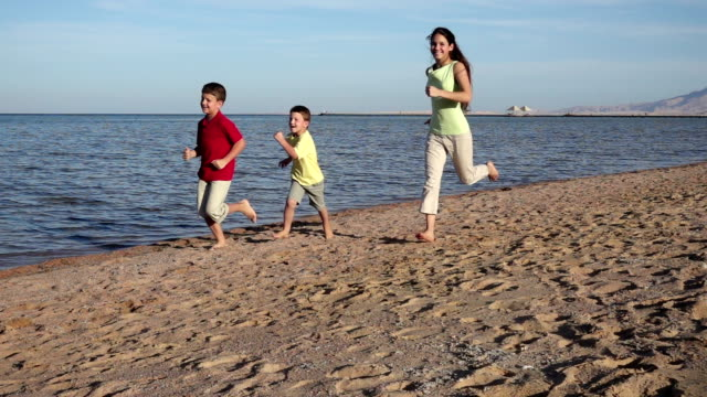 Group of three kids running at the beach in Egypt resort, slow m video