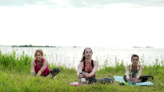 Group of three mature women practicing yoga outdoors. Women doing seated single leg head-to-knee forward bend on mats placed on grass near lake, tracking shot. Yoga instructor explaining exercise