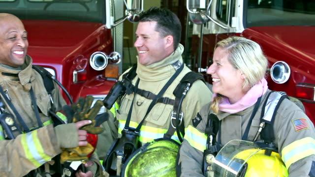 Grupo de tres bomberos y multiétnicos en la estación - vídeo