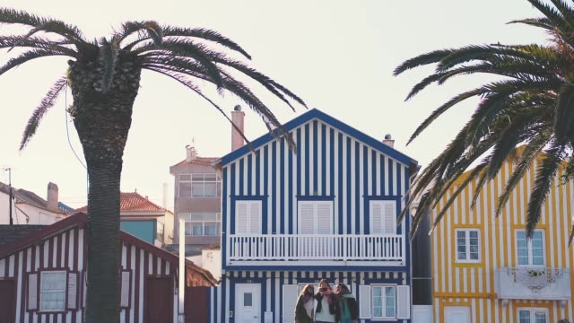 vídeos de stock e filmes b-roll de group of tourist friends sightseeing and traveling across the portuguese coast. famous fisherman houses on aveiro city - aveiro