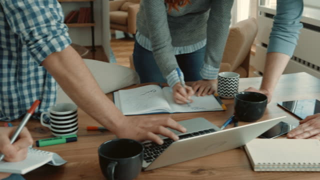 Group of unrecognizable freelancers using laptop and writing down a busines plan in the office. video