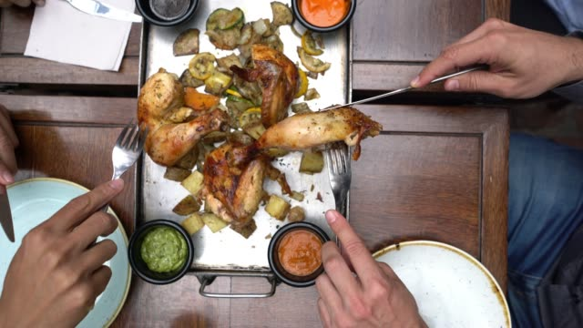 Group of unrecognizable people sharing roasted chicken and each serving on their plates video