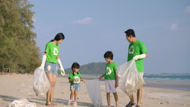 Group of volunteers in green t-shirts cleaning up the beach with plastic bags full of garbage. Slow Motion. Safe ecology concept. 4k resolution.