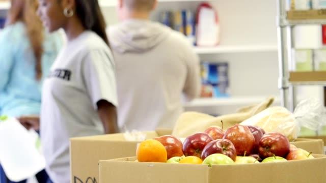 Group of volunteers organize food bank storage room