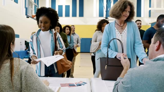 Group of voters receive ballots at polling place A large group of male and female voters receive a ballot from polling place volunteers on election day. The volunteers also give instructions to the voters and answer their questions. register stock videos & royalty-free footage