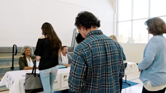 vídeos y material grabado en eventos de stock de grupo de electores espera en la fila para recibir la boleta electoral el día de la elección - polling place