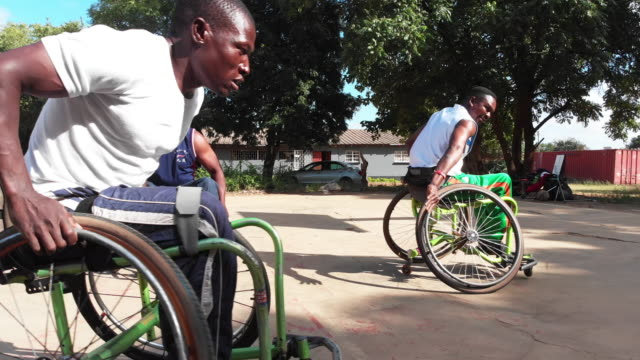 Group of Wheelchair Basketball Players Fast Circling around the Ground Africa, Sports, Basketball - Physically Challenged Basketball Team Players on the Ground playing a friendly match on a summer day. amputee stock videos & royalty-free footage