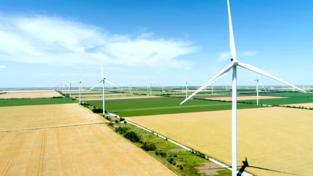 group of windmills for electric power production in the agricultural fields - энергия ветра стоковые видео и кадры b-roll