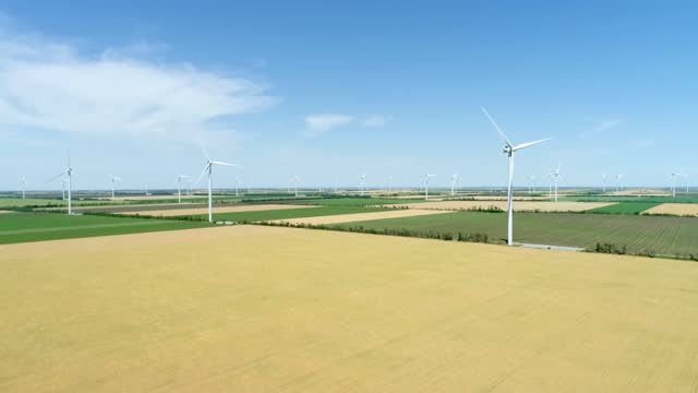 Group of windmills for electric power production in the agricultural fields. Aerial view.