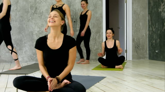 Group of women coming to a yoga class for a practice, yoga trainer is waiting video
