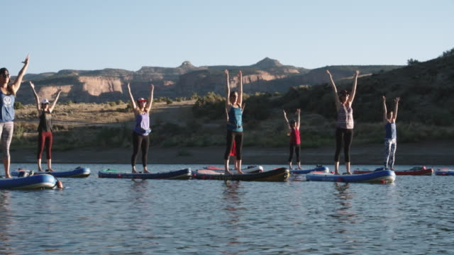 A Group of Women in Mountain Pose/Upward Salute Yoga Position on Paddleboards on a Desert Lake Under a Clear, Blue Sky with a Mesa in the Background in Western Colorado (Snooks Bottom) A Group of Women in Mountain Pose/Upward Salute Yoga Position on Paddleboards on a Desert Lake Under a Clear, Blue Sky with a Mesa in the Background in Western Colorado (Snooks Bottom) athleticism stock videos & royalty-free footage