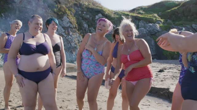 海で泳ぐ準備をしながら、一緒に笑って楽しむ女性のグループ。 - disruptagingcollection点の映像素材/bロール