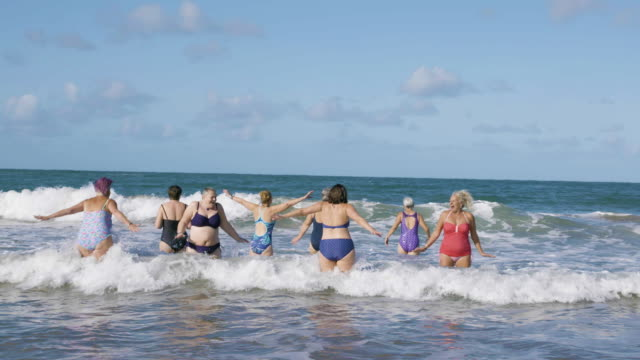a group of women swimmers laughing and jumping around as they get into the cold sea for a swim. - body positive video stock e b–roll