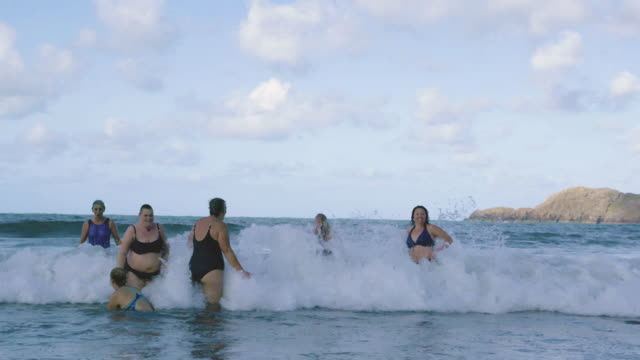 a group of women swimmers laughing and jumping around in the cold sea. - aktywny tryb życia filmów i materiałów b-roll