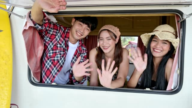 Group of young asian friends opening window greeting and waving inside of campervan