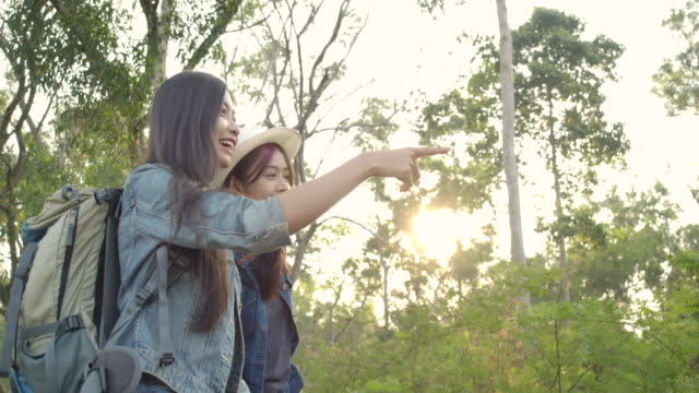 スローモーション-田舎のハイキングの冒険に若いアジアの女の子のグループ。森のハイカーキャンプ。旅行と友情の概念。 - バックパッカー点の映像素材/bロール