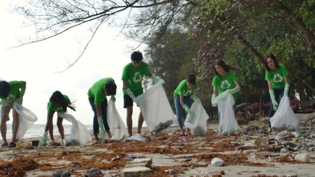 gruppe junger asiatischer menschen freiwillige in grünen t-shirts putzen den strand mit plastiktüten voller müll. sichere ökologie konzept. 4k auflösung. - verantwortung stock-videos und b-roll-filmmaterial
