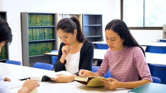 stockvideo's en b-roll-footage met groep van jonge aziatische leren van leerlingen met boek en het doen van onderzoek in college library, onderwijs en school concept - literatuur